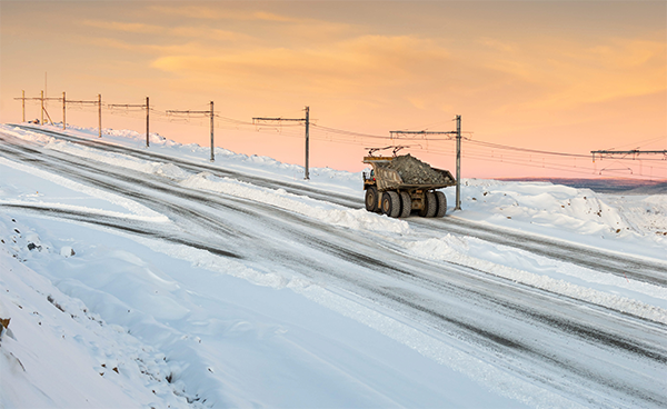 Electric trolley line and mine truck in snowy landscape